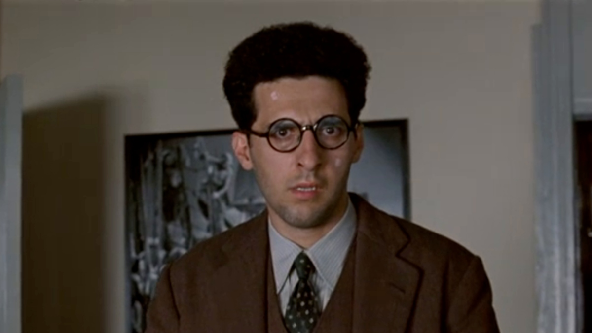 Barton Fink still of main character wearing brown suit, tie, and round glasses with a confused look