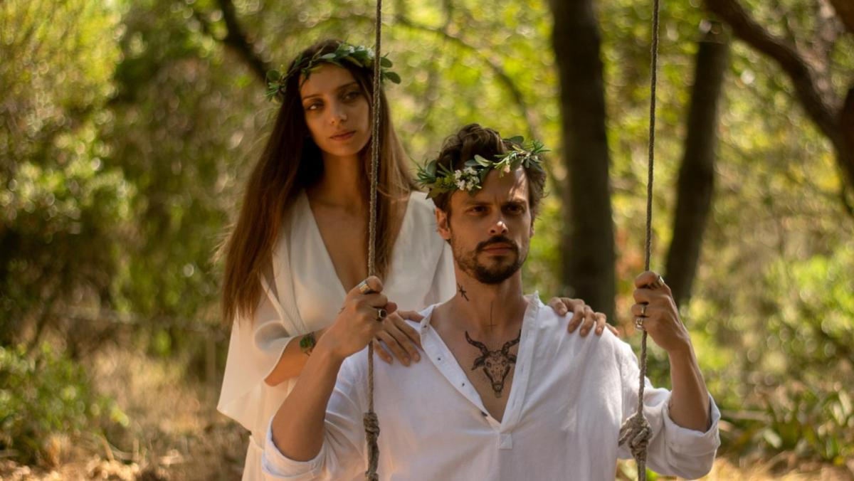 A still from King Knight shows a woman and man sitting on a sing wearing flower crown