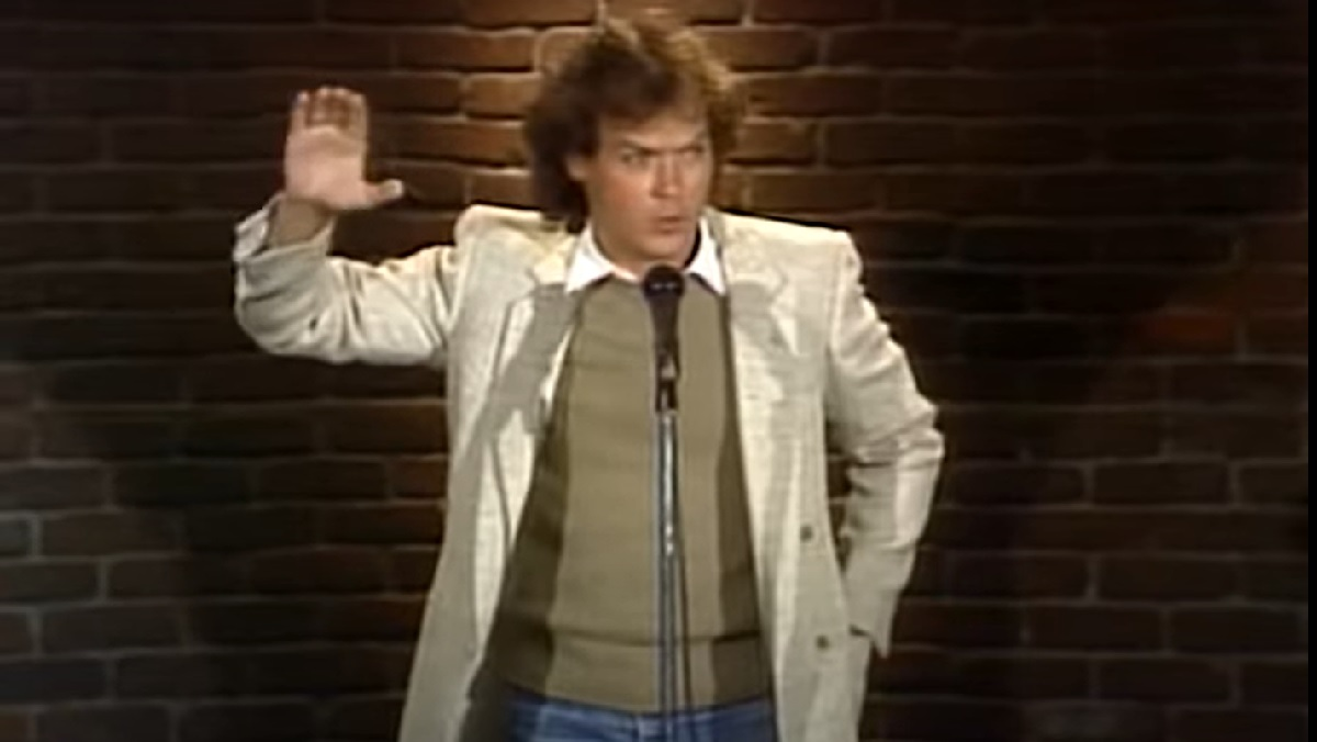 A very young Michael Keaton, from 1981's An Evening at the Improv, wears jeans, a sweater over a button-down shirt, and a long raincoat as he gestures with his right hand as he speaks into a microphone. Behind him, the famous brick wall of the Improv.