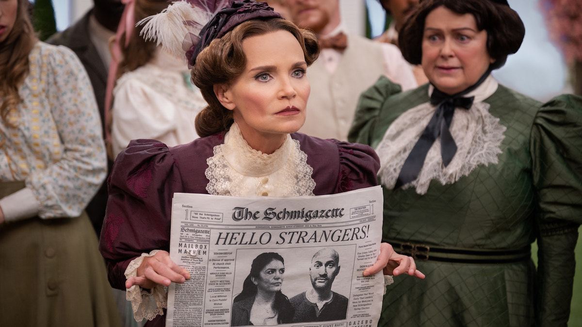A woman angrily holds a newspaper front page open