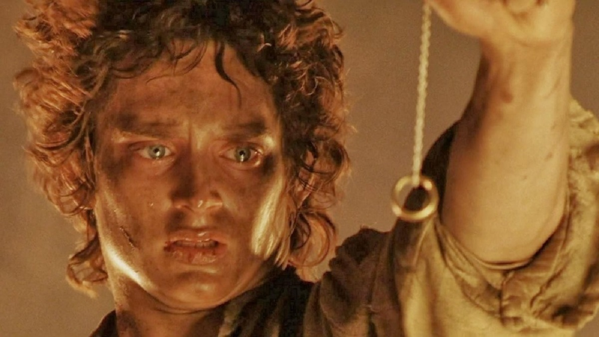 Elijah Wood as Frodo Baggins holding the One Ring