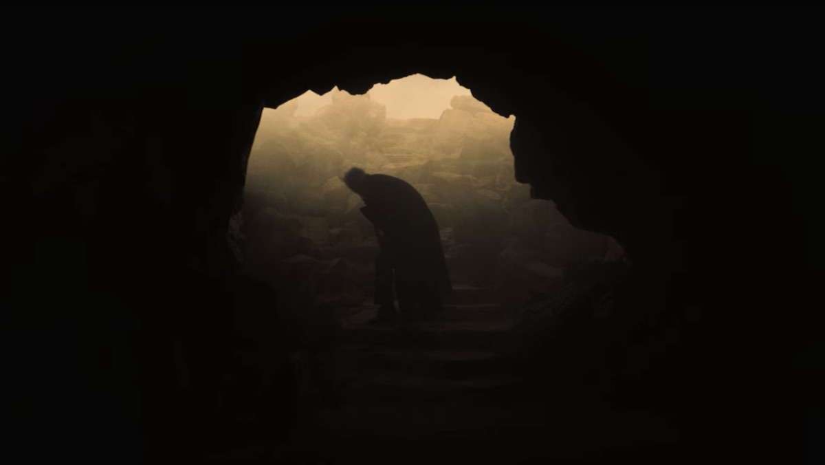 A man stands hunched over in the lighted mouth of a dark cave in the desert on Midnight Mass