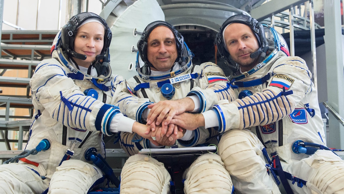 Three cosmonauts sitting together in space suits holding hands