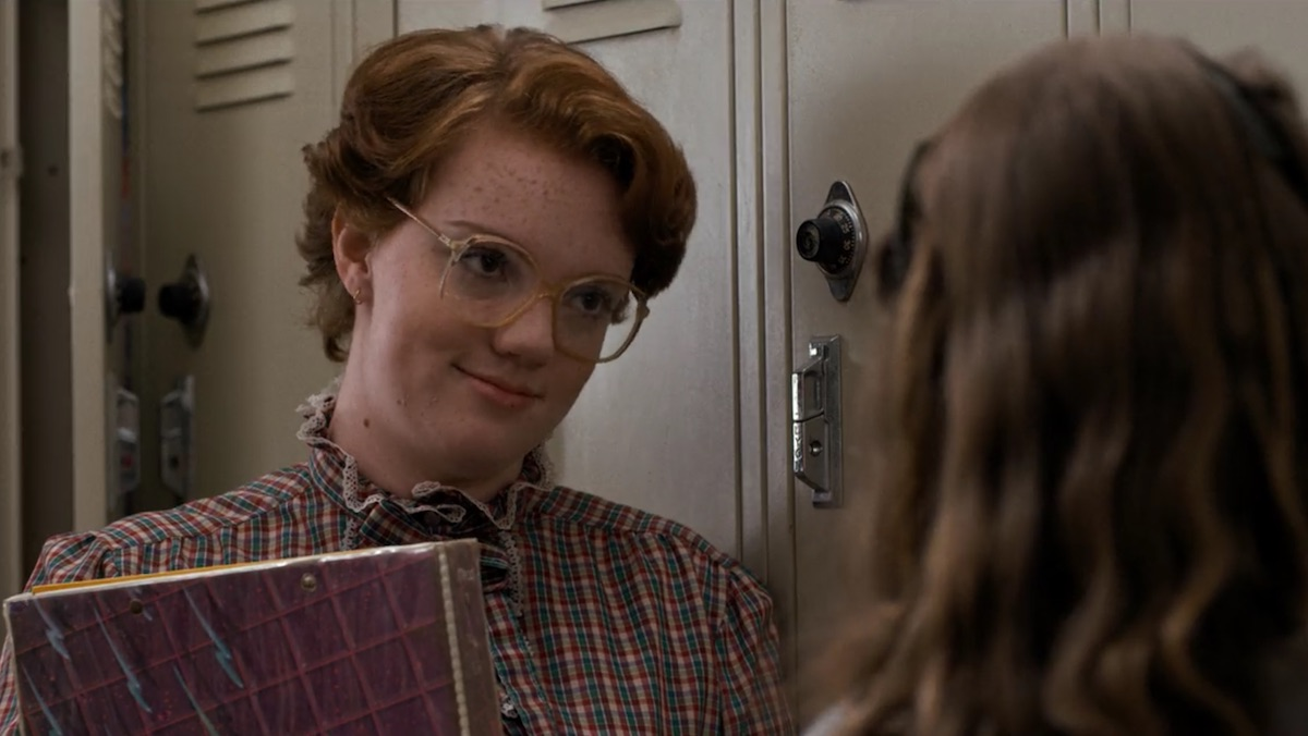 Barb wears glasses and holds her books in front of lockers on Stranger Things