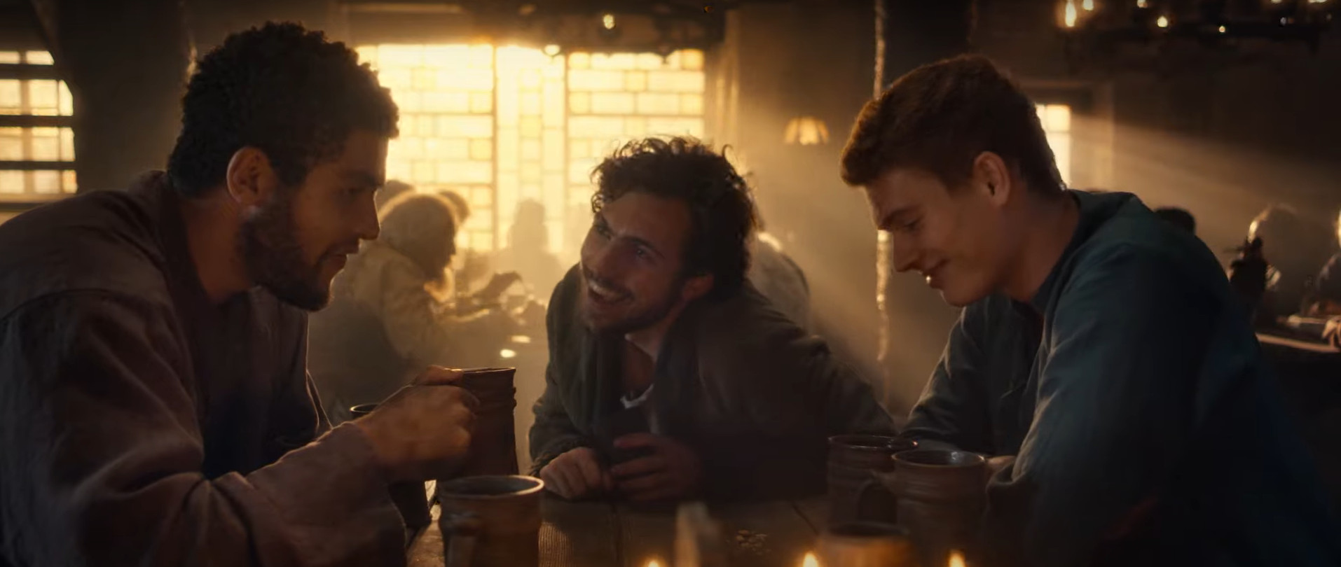 Three men sit at a table with drinks