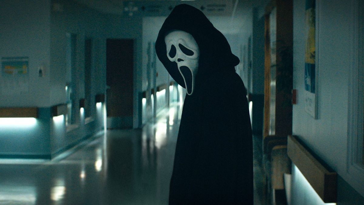 ghostface from scream 2022 stands in a hallway facing the camera