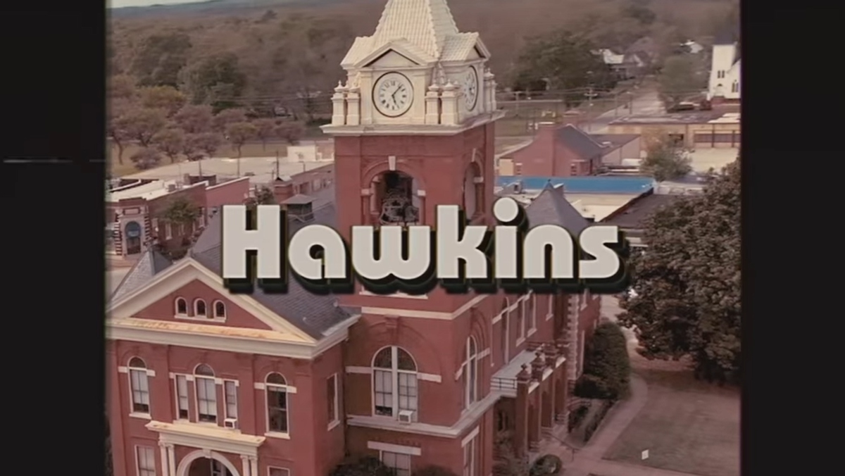photo of a tower with a church and the words Hawkins in white letters over it