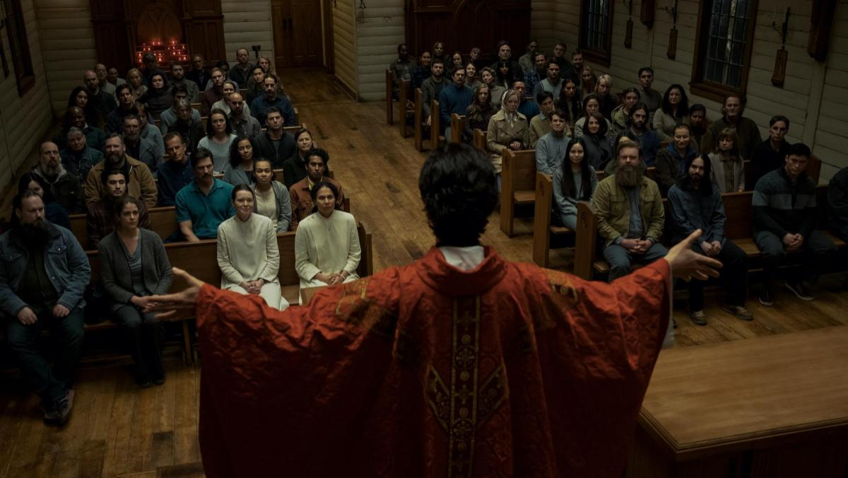 A still from Midnight Mass shows Father Paul speaking to his parishioners in church